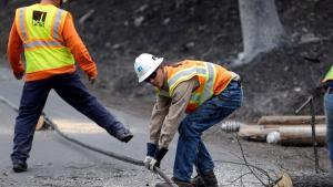 Utility crews clear roads during a fire. AP Photo Elaine Thompson