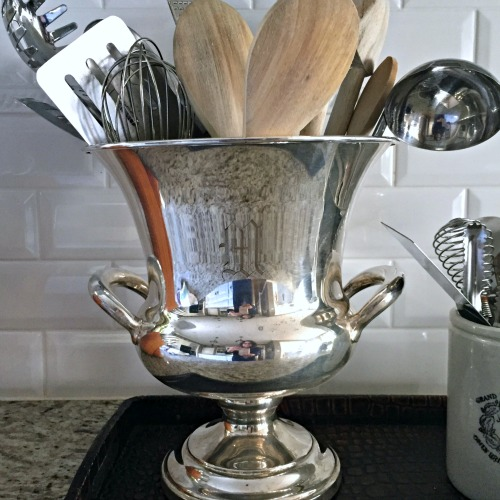 monogrammed silverplate champagne bucket used as kitchen utensil holder
