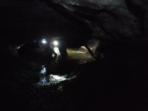 About to enter the deep cave waters - notice the headlamps and shadow of the cavers ahead. Photo copyright Sara J. Bruegel, 2015