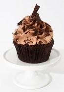 Cupcake au chocolat avec glaçage meringue suisse au chocolat et à la fraise, garni de copeaux de chocolat