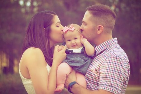 Parents kissing baby during naming ceremony