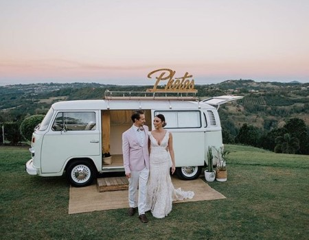 Bride and groom standing before kombi van photo booth at their fun wedding