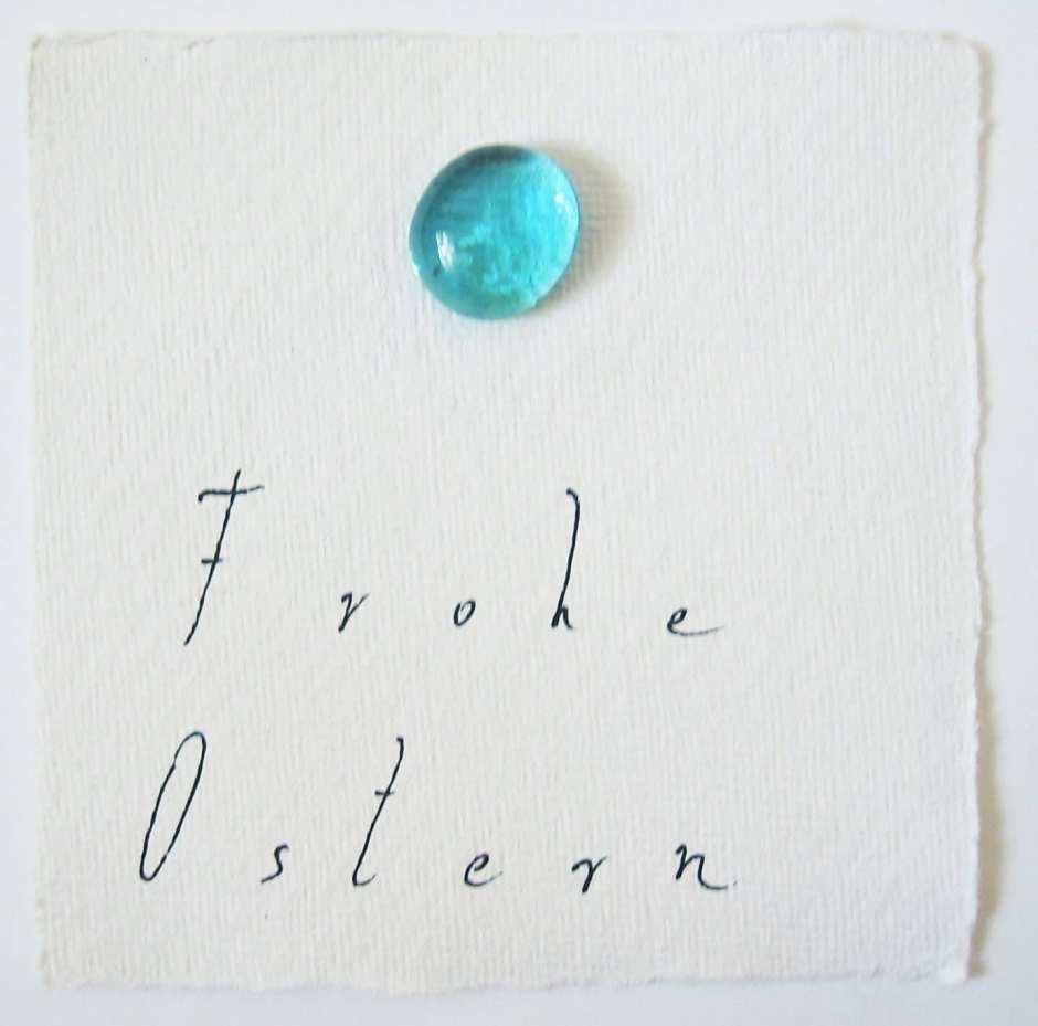 Du siehst einen marineblauen Glasstein auf der Osterkarte und die Schrift Frohe Ostern