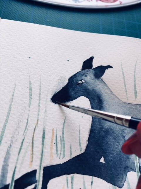 Du siehst hier, wie Dodo die Schnauze des Aquarell Wiesenhüpfender Whippet malt.