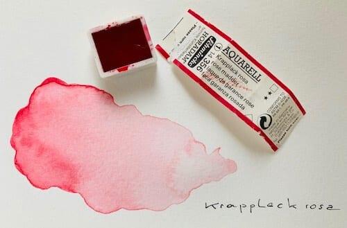 Man sieht ein Näpfchen vol Krepplack-Rosa von Schmincke und einen Testfleck der Aquarellfarbe für Creative Club