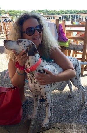 Man sieht die Künstlerin Dodo Kresse mit einem Dalmatiner in Ibiza