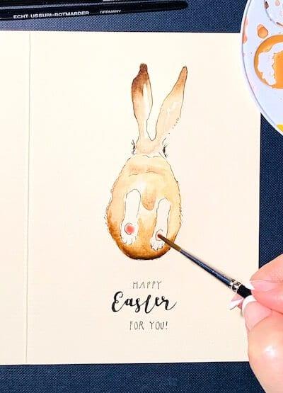 Man sieht eine Osterkarte, gemalt von Dodo Kresse für Creative Club , die Pfoten in Rosa