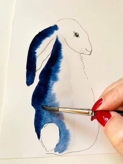Man sieht die Osterhasenzeichnung von Dodo Kresse und wie die Künstlerin langsam die indigoblaue Farbe in den Hasenkörper vermalt.