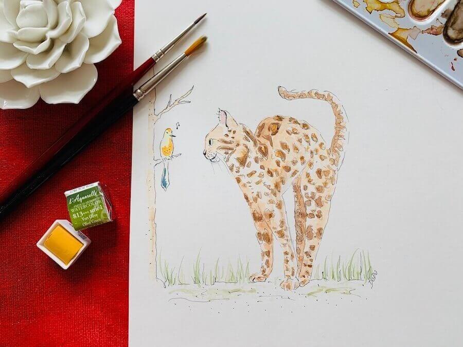 Hier siehst du das Aufmacherbild des Artikels. Mit Aquarellfarben habe ich eine Bengal Katze gemalt, bzw. illustriert. Der Hintergrund ist rot, zwei Aquarellfarben liegen daneben in Grün und Gelb.