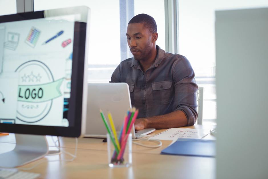 Serious graphic designer using laptop in creative office
