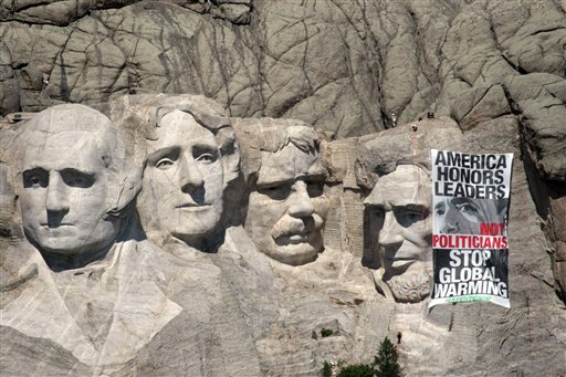 In this picture provided by the environmental group Greenpeace, Greenpeace climbers rappel down the face of Mount Rushmore National Memorial in Keystone, S.D. on Wednesday, July 8, 2009 to unfurl a banner that challenges President Obama to show leadership on global warming. Obama is at the G8 meeting in Italy  to discuss the global warming crisis with other world leaders. A federal prosecutor says a dozen people were taken into custody on Wednesday after the incident. (AP Photo/Greenpeace, Kate Davison)