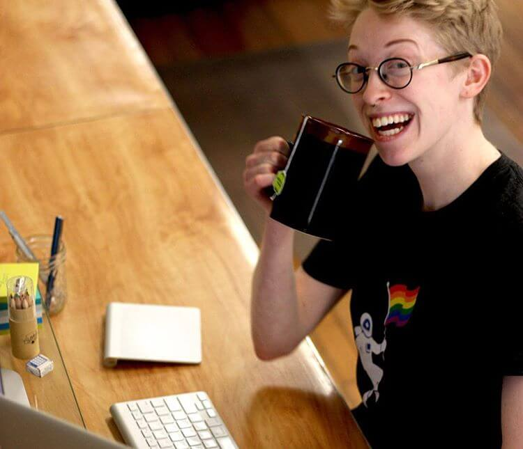 Milo smiling and drinking tea while working at Moonfarmer