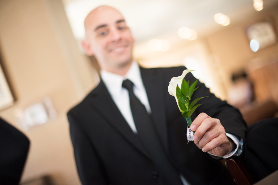 Groom holds out his boutonniere