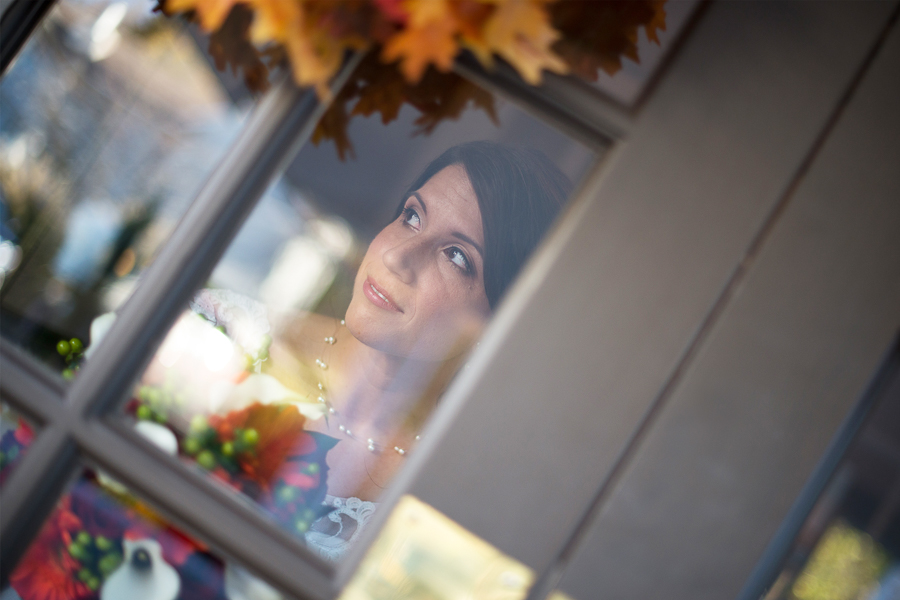 Photo taken from outside of a bride looking through the window
