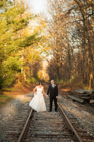 Birde and groom walk along railroad tracks