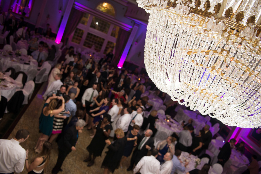 Chandelier shot with guests dancing in background in Mendenahall Grand Ballroom