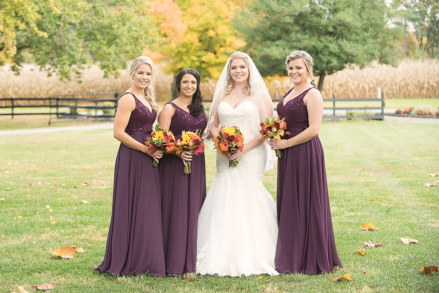 Bride and bridesmaids group shot with a rustic wooden fence and fall foliage in the background