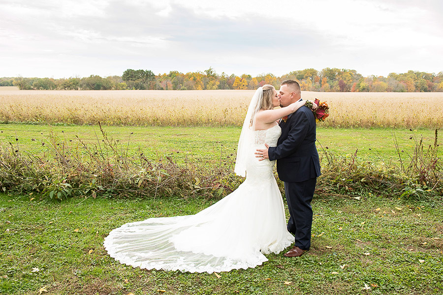 A bride and groom kiss in front of a field in Fall