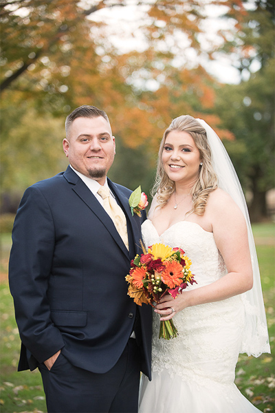 Bride and groom smile at camera with fall leaves in the background
