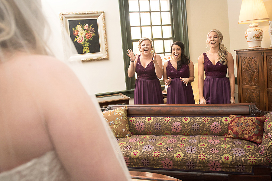 Three bridesmaids are excited to see how beautiful the bride looks in her wedding dress