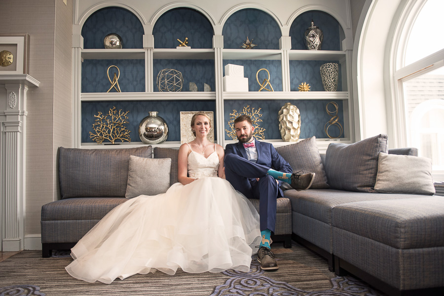 Couple sits on large sectional in the club room for a serious looking but fun photo