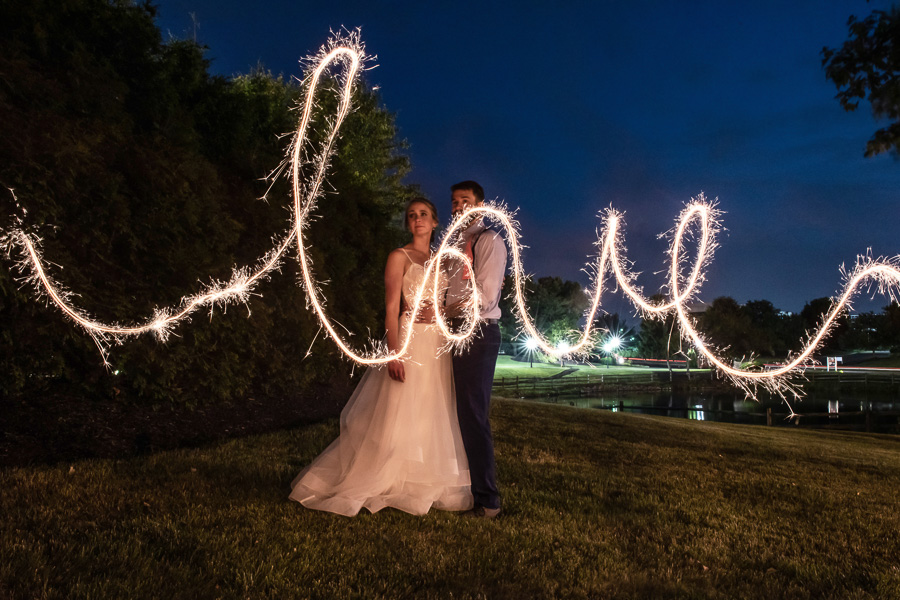 Night time photo of bride and groom posing with the word love written with a sparkler in front of them