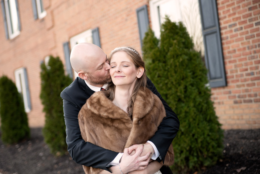 A groom hugs and kisses his bride on the cheek outside