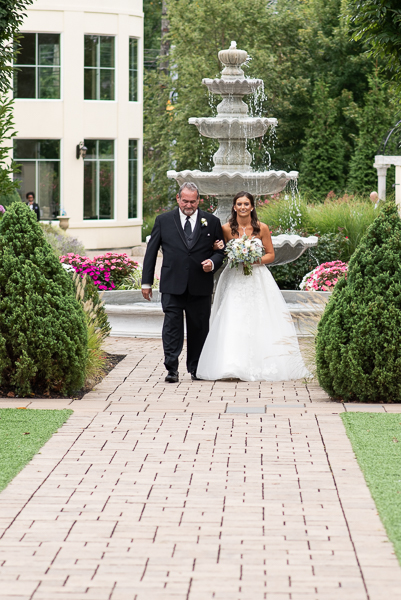 Brides father walks her down the aisle at Waterfall wedding