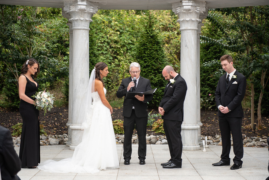 Couple and bridal party praying during ceremony