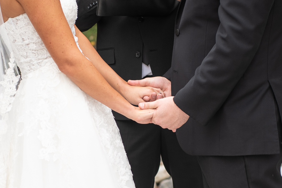 Close up of bride and groom holding hands during ceremony