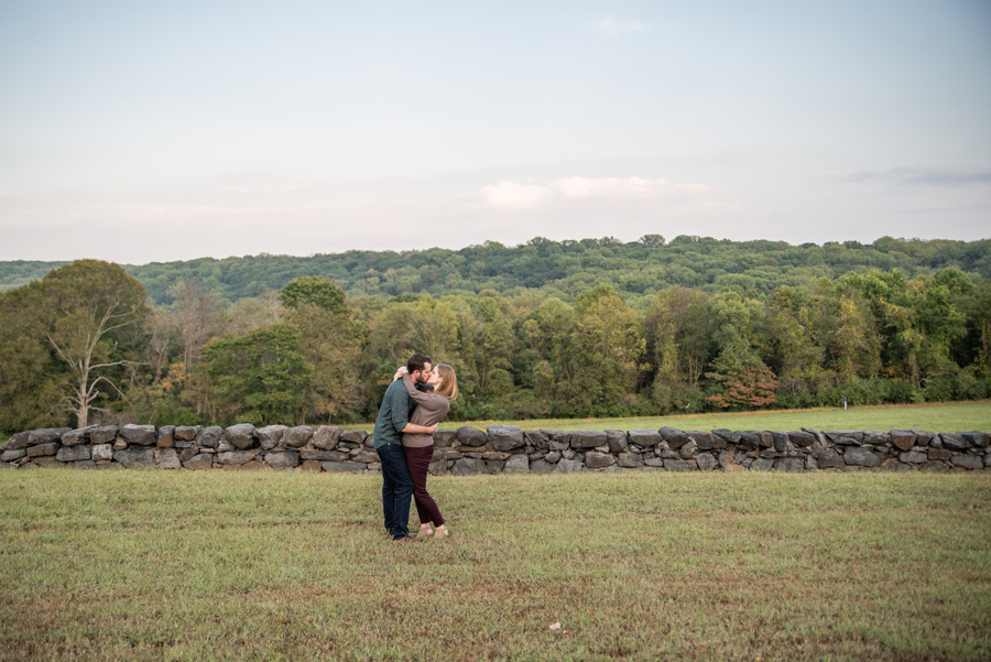 Engaged couple kissing with view of Brandywine Creek State Park behind them
