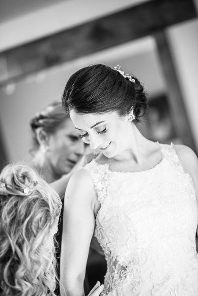 Black and white picture of the bride looking down while bridesmaids help her with the back of her dress