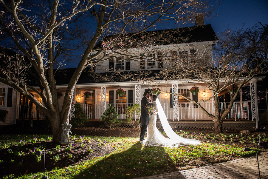 Night shot of the bride and groom standing in front of The Farmhouse in Delaware with a pop of light flashing behind them
