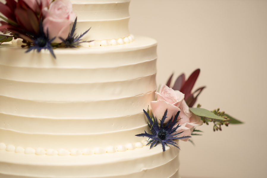Closeup of thistle and rose on wedding cake at The Farmhouse in Delaware