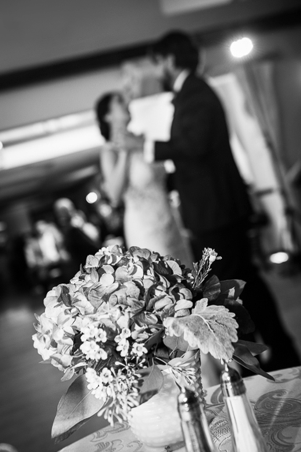 Black and white picture focusing on flowers with bride and groom dancing in the background blurred out