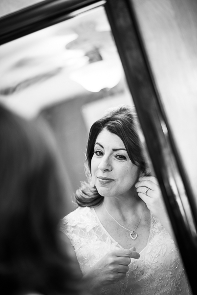 Black and white bride puts earring in while looking in mirror