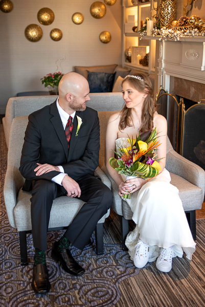 Bride and groom smile at each other in club room of Hilton Christiana