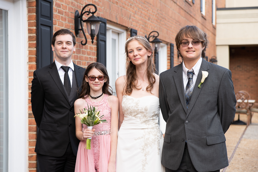 A courtyard portrait of the bride and her siblings at Hilton Christiana wedding