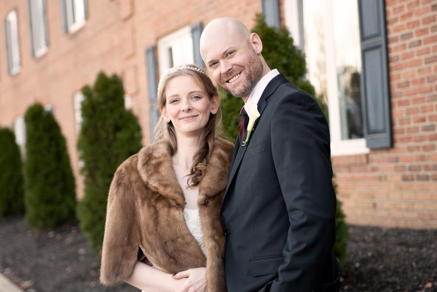 Outdoor portrait of bride and groom smiling toward camera