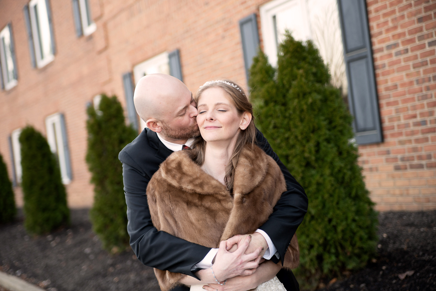 Groom wraps his arms around bride and kisses her cheek outside the Hilton Christiana