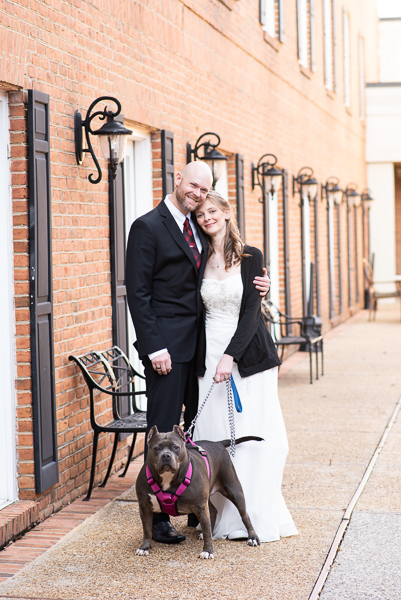 Portrait of bride and groom with their dog in the courtyard of the Hilton Christiana
