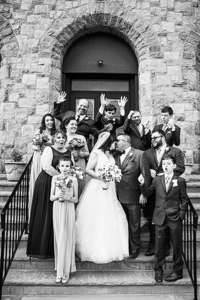 November wedding party makes funny faces while bride and groom kiss