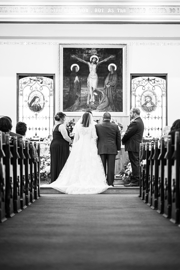Black and white of bride and groom standing at the front during wedding ceremony