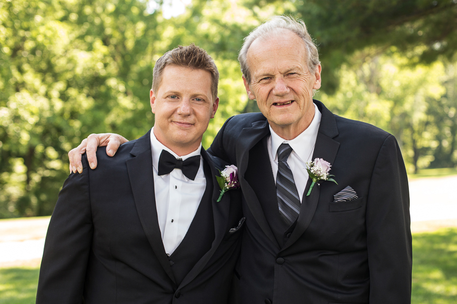Groom and his dad smiling at the camera