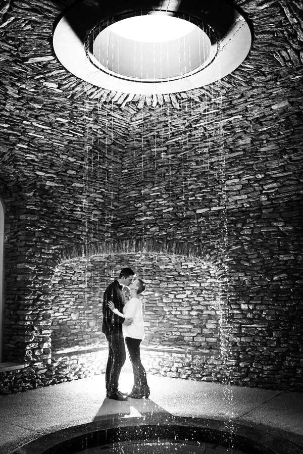 Black and white photo of couple kissing behind a shower like fountain