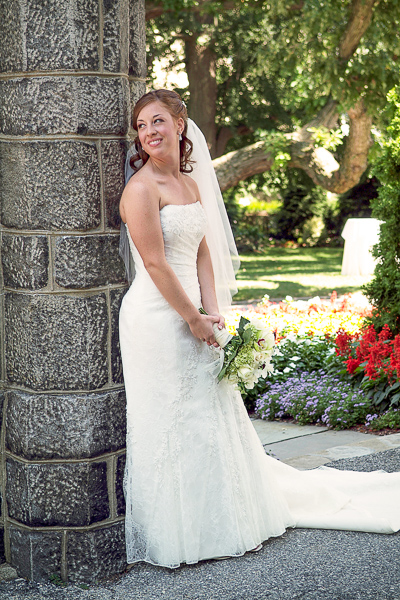 Bride poses along stone column