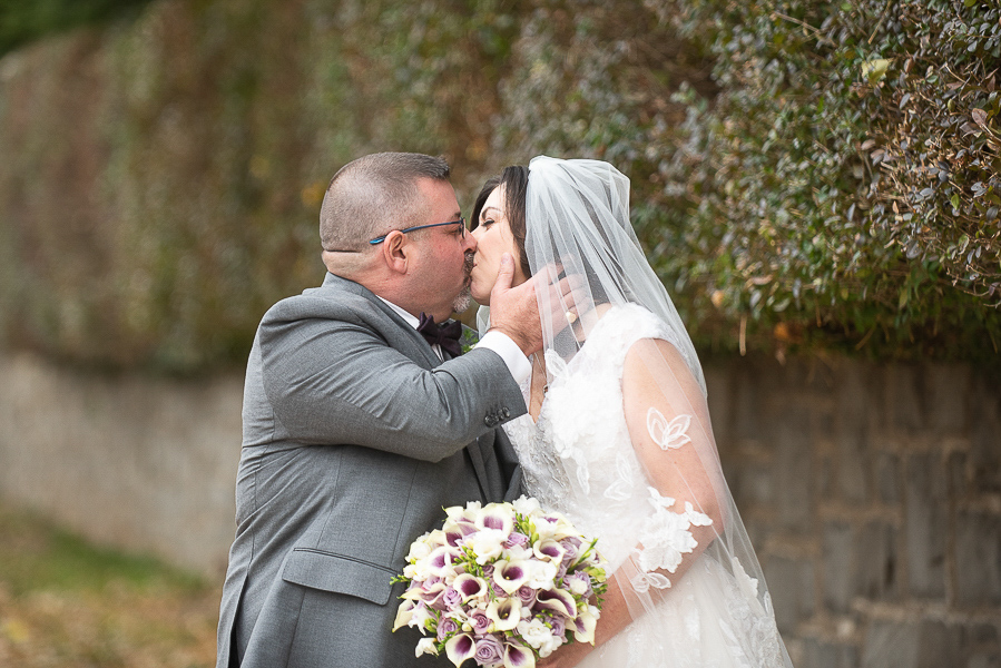Groom reaches for his bride's face to kiss her