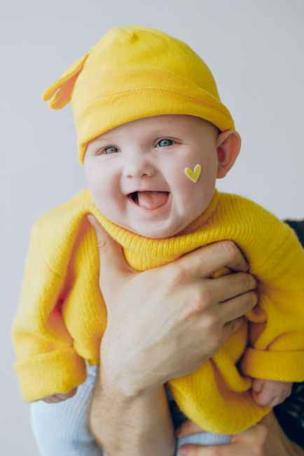 baby in yellow knit cap and yellow knit sweater