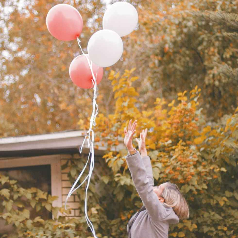 woman in gray jacket released balloons in the air