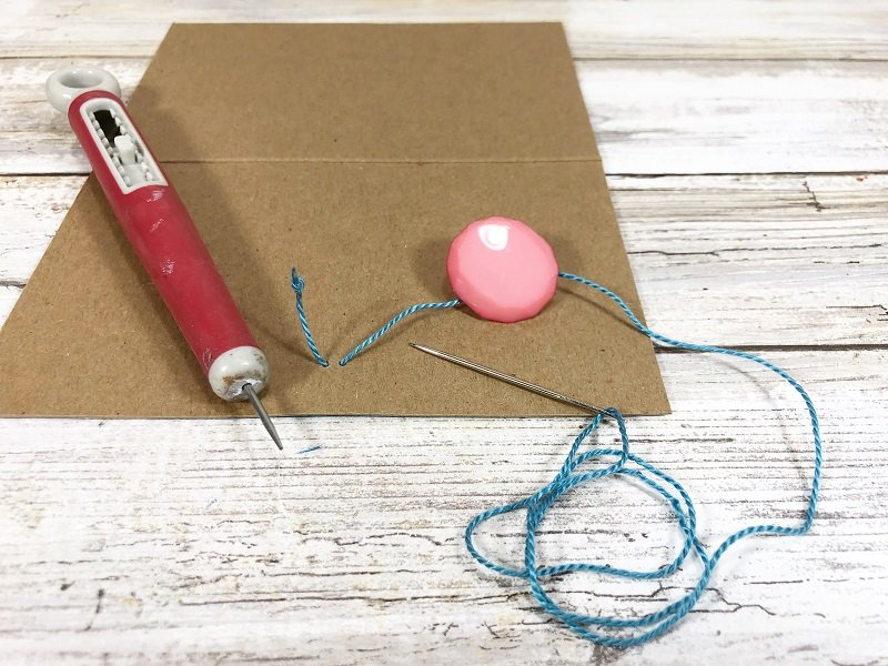 Sew a colorful button onto the front cover with a needle and embroidery floss #creativelybeth #recycled #crafts #notebooks #journals #upcycled